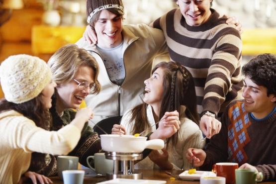 Молодые люди едят фондю– национальное блюдо Швейцарии