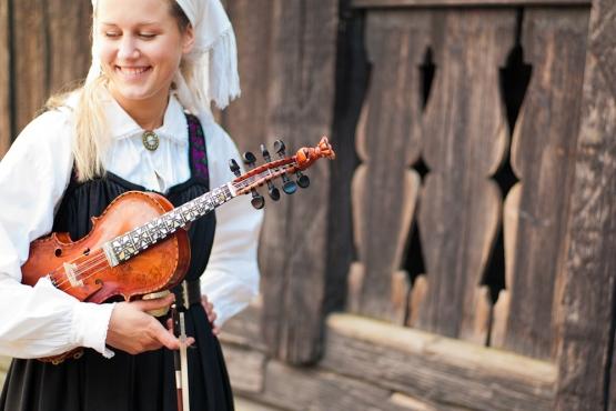 Девушка в национальном костюме с хардангерфелем