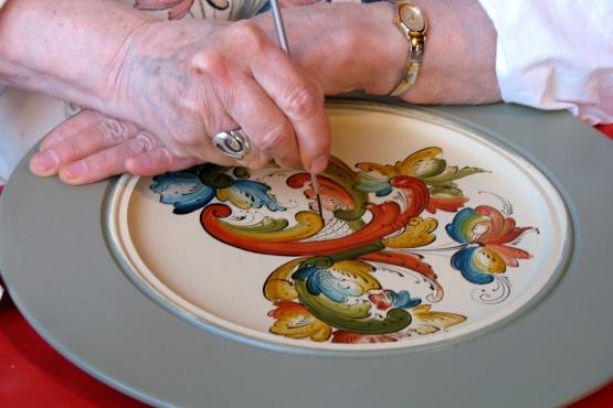 Мастерица украшает блюдо традиционной норвежской живописью– росемалингом